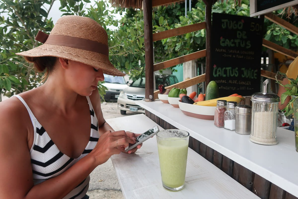 Kim checking her phone sipping a green smoothie in Tulum, Mexico.. or maybe looking for travel insurance when already traveling.