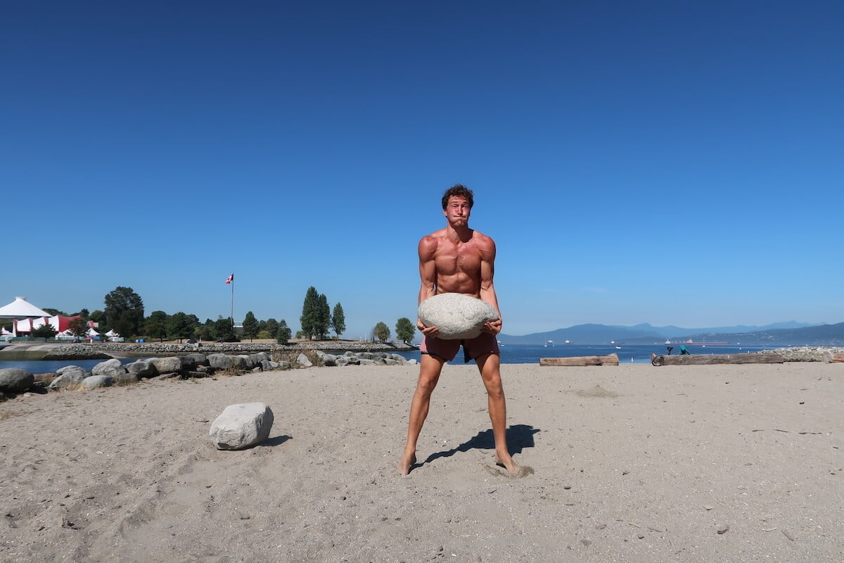 Chris lifting a big rock at the beach.