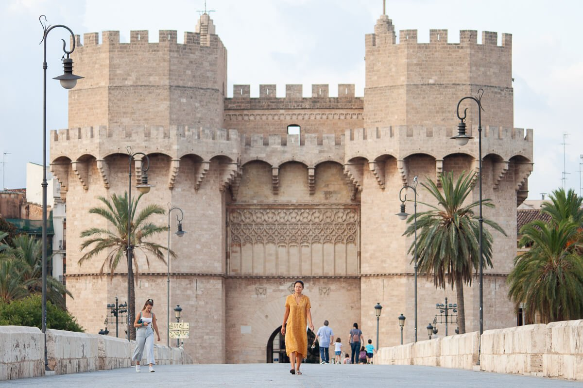 Is Valencia worth visiting cover image of Kim walking in front of the Torre de Serranos