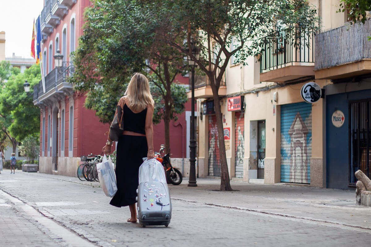Valencia woman rolling small suitcase and plastic bags over street in El Carmen neighbourhood.