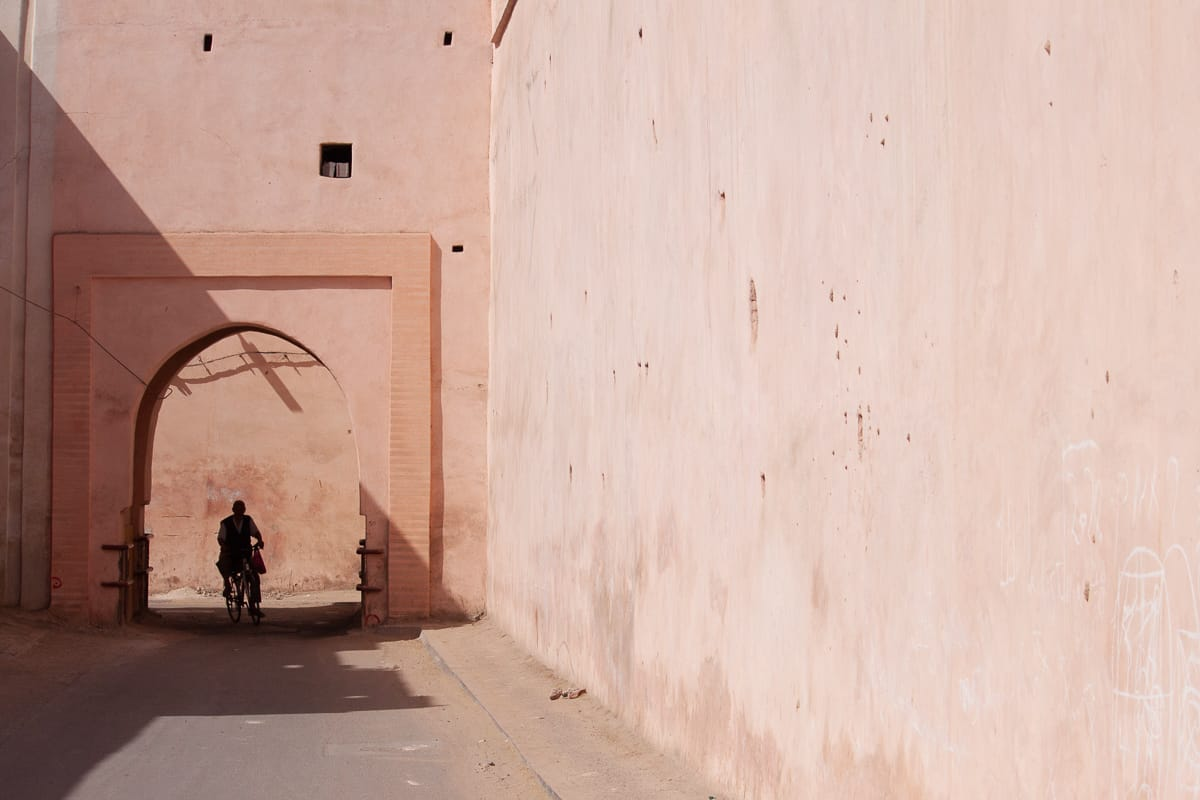 Pink walls and Moroccan man biking in Marrakech.