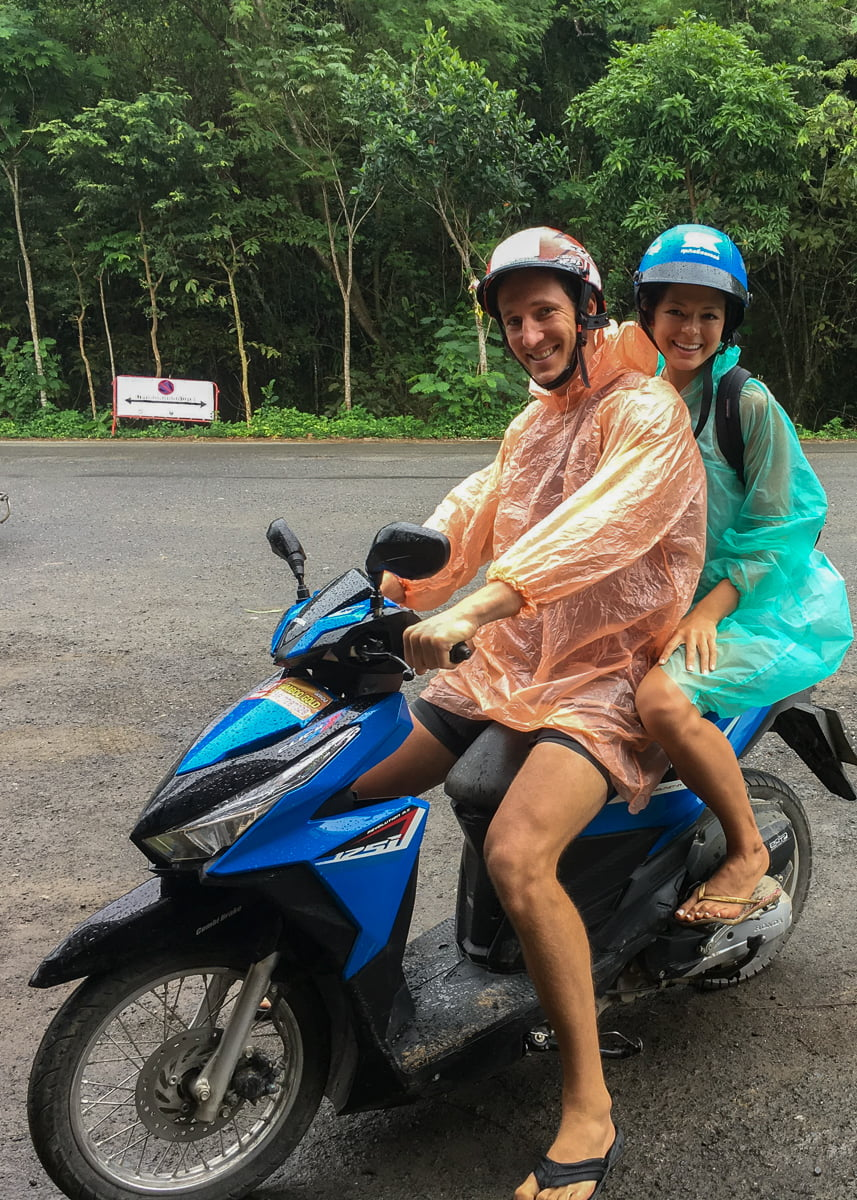 Chris and Kim on a motorycle wearing plastic raincoats