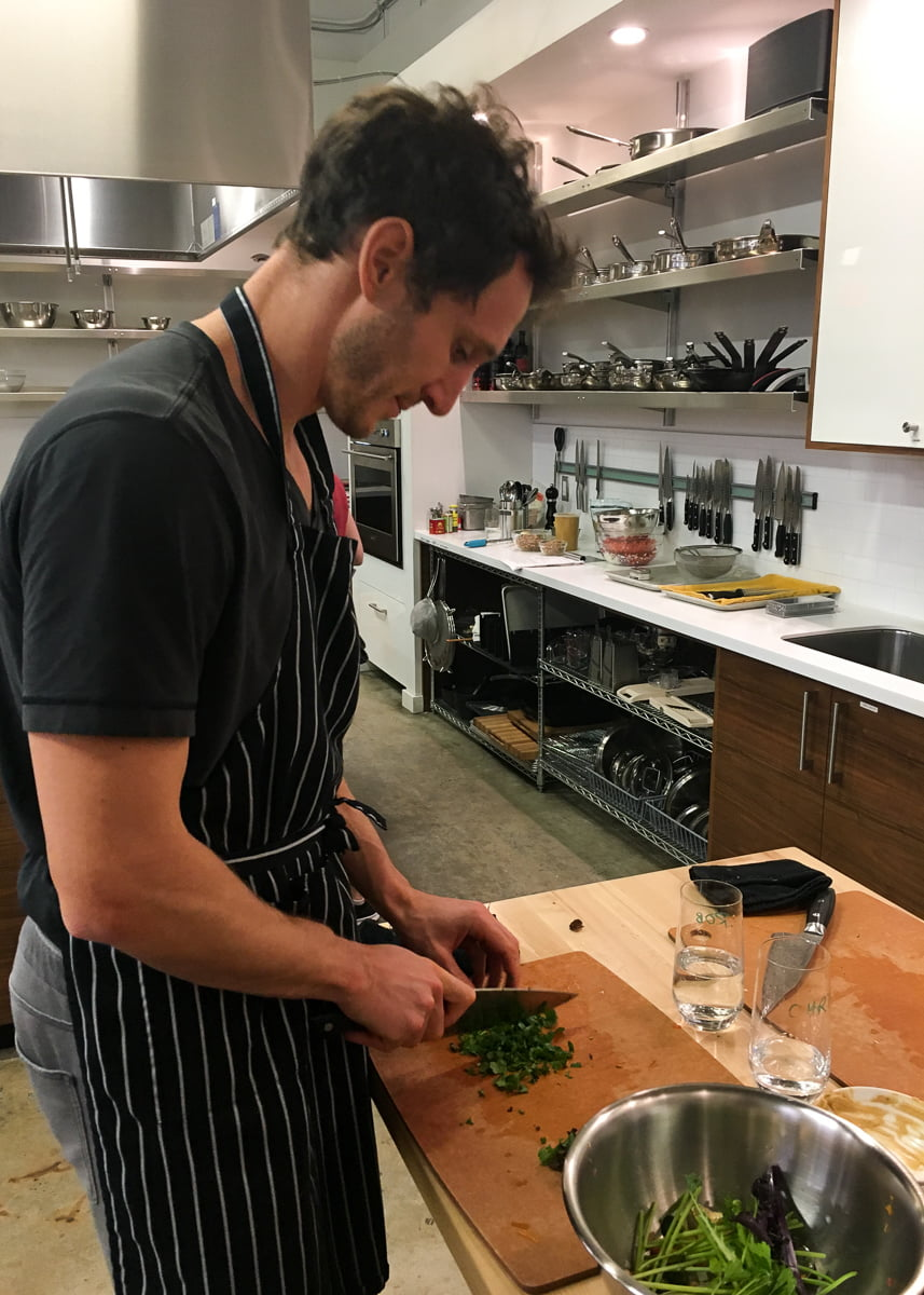 Chris chopping up greens in a knife skills class