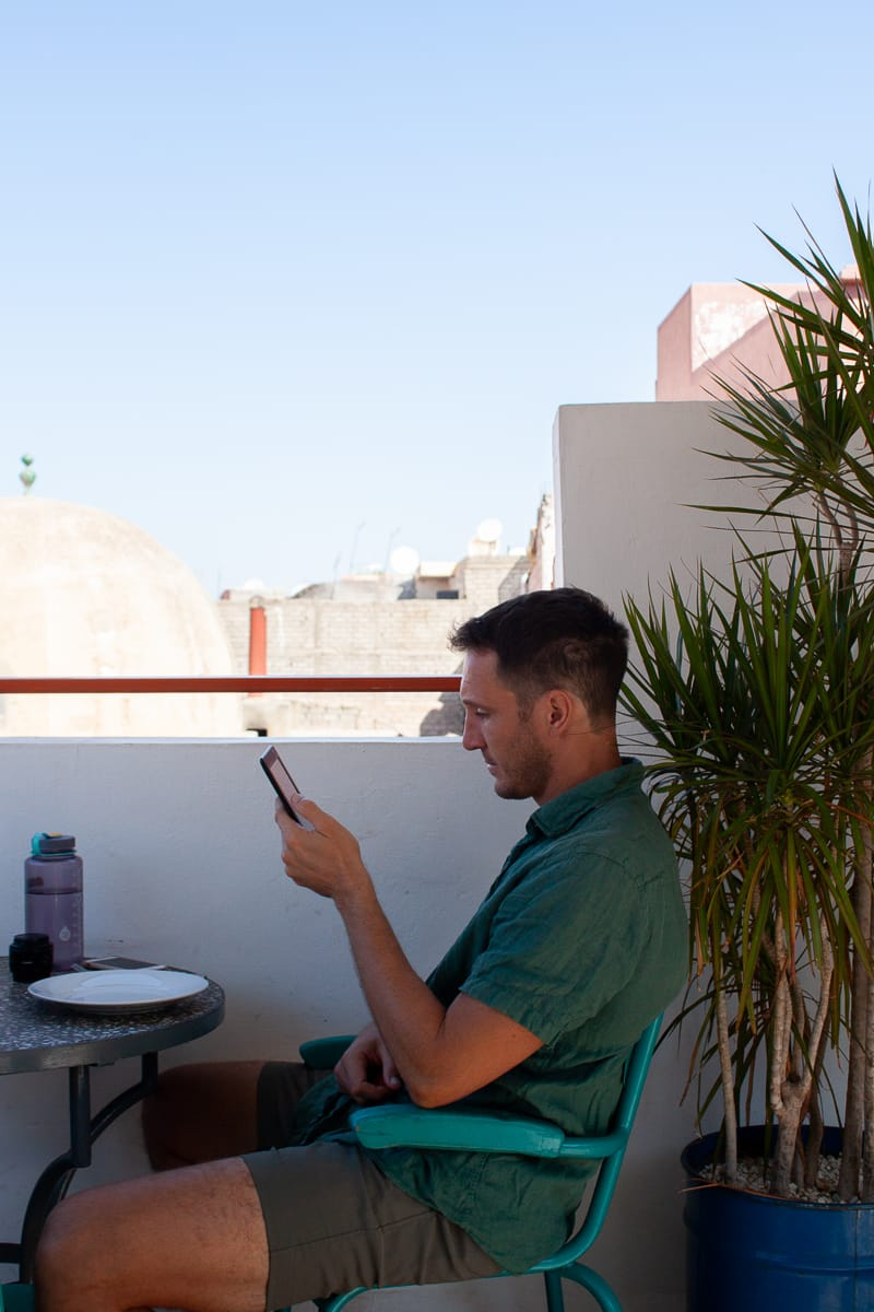 Chris reading his kindle at a cafe in Marrakech.