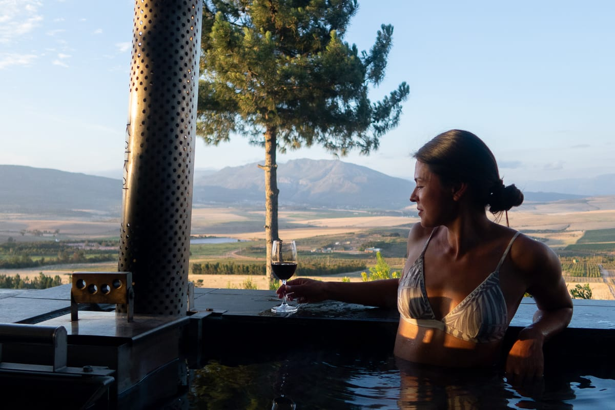 Kim about to take a sip of wine inside our Airbnb's wood-fired hot tub in Bot River, just outside of Cape Town.