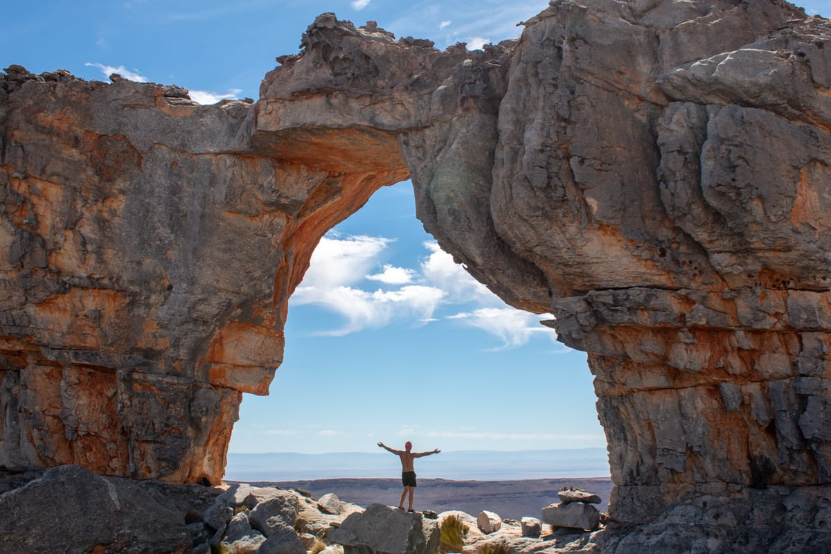 Prolonged fasting benefits cover image of Chris standing under Wolfberg Arch in South Africa
