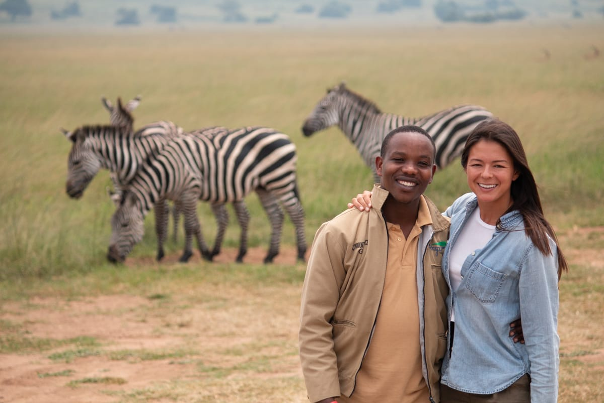 Our guide Samuel and Kim post in front of zebras in Akagera Park