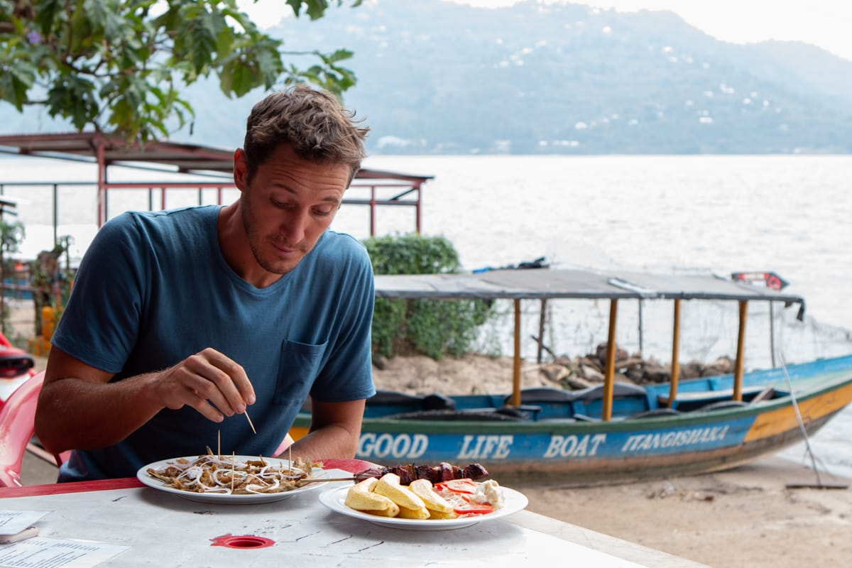 Chris eats sambaza at Lake Kivu