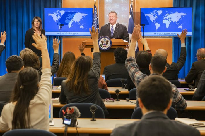 Journalists with hands up for questions at a press conference