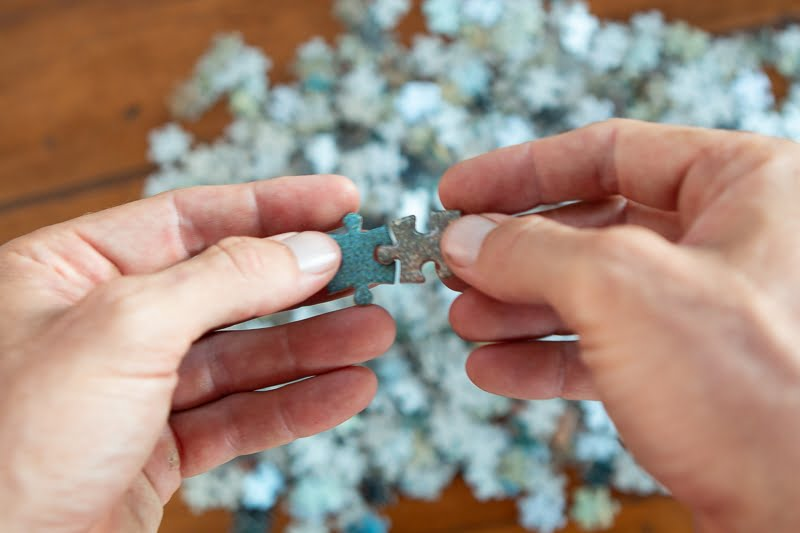 Hands putting the puzzle pieces together