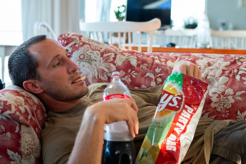Character missing direction in life eating chips and drinking soda