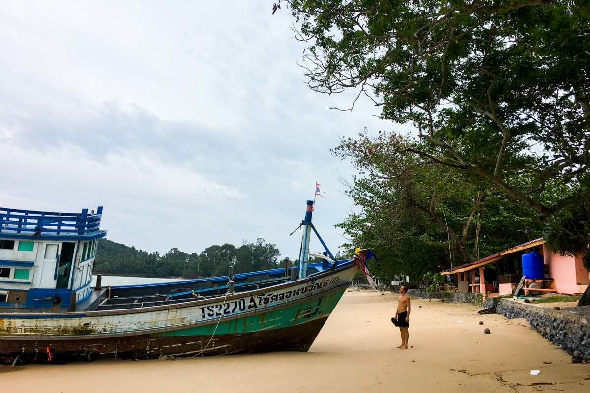 Chris stands beside boat washed up on beach in Thailand.
