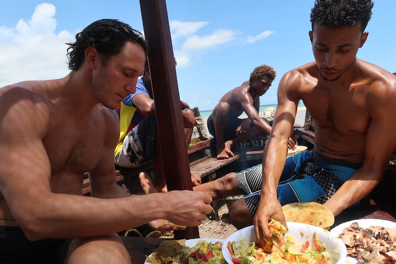 Eating salad and fish with our hands with friends on a boat in Kenya