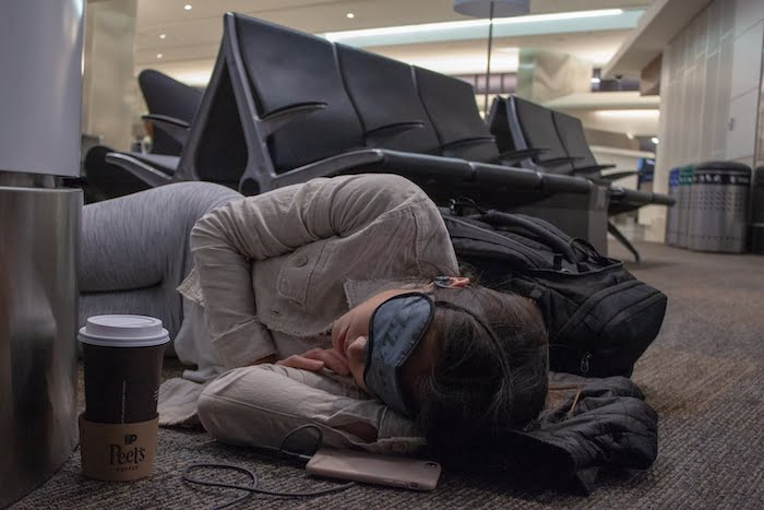 Kim sleeping on the floor in an airport