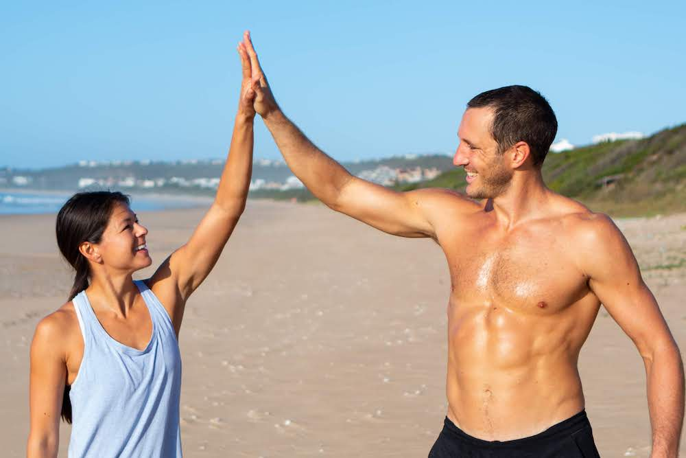 Health and fitness page cover of Chris and Kim high-fiving on the beach